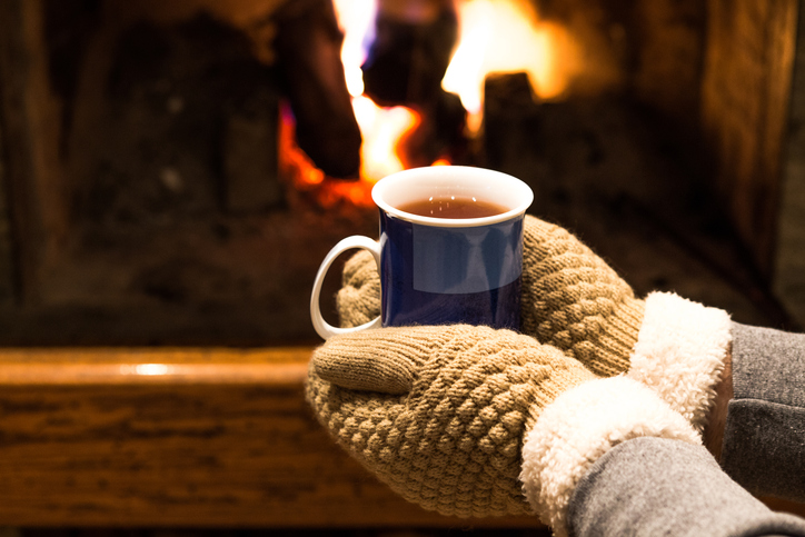 Hands with warm gloves holding blue cup of tea in front of fireplace at home