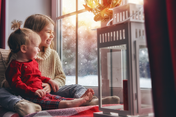 Merry Christmas and happy holidays! Cute little children girls sitting by the window and looking at the winter forest. Room decorated on Christmas. Kids enjoy the snowfall.