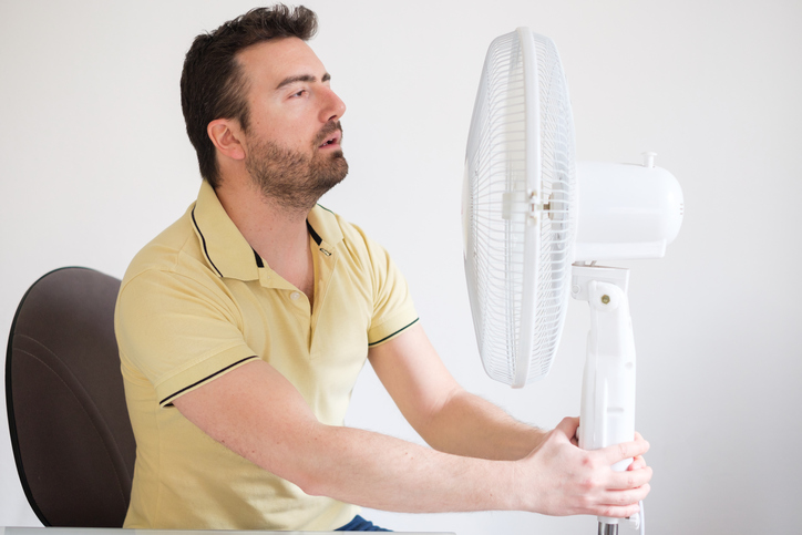 Man refreshing in front of air electric fan